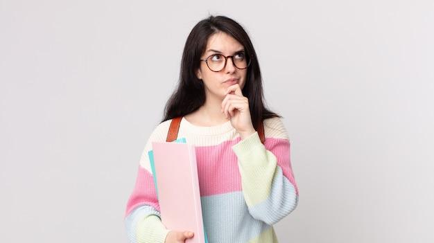 Ładna kobieta myśli, wątpi i jest zdezorientowana. koncepcja studenta uniwersytetu