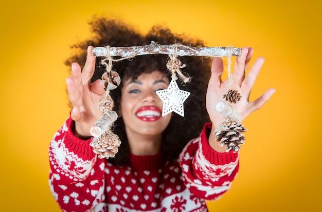 Ładna kobieta na boże narodzenie świąteczne dekoracje żółte tło