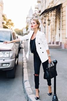 Ładna kobieta na piętach łapie taksówkę w mieście. w ręku trzyma torbę.