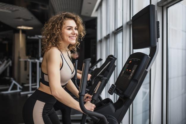 Ładna kobieta na siłowni, robi ćwiczenia