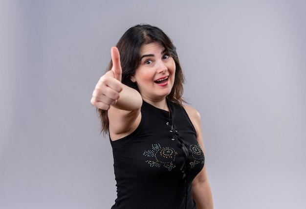 Ładna kobieta na sobie czarną bluzkę robi szczęśliwym kciuki do góry