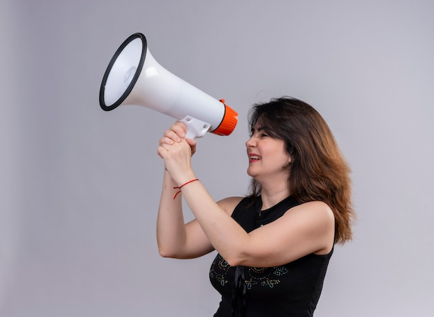 Ładna kobieta na sobie czarną bluzkę trzymając gramofon szczęśliwie zamykające oczy na szarym tle