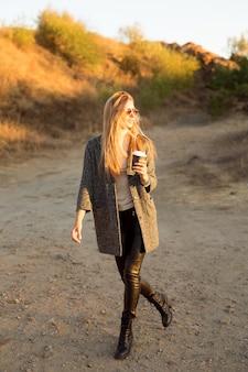 Ładna kobieta na zewnątrz z poranną kawą