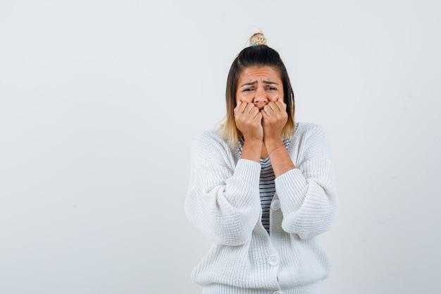 Ładna kobieta naciskając ręce na twarz w koszulce, swetrze i patrząc na depresję