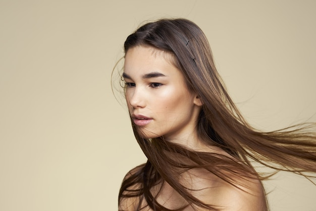 Ładna kobieta nagie ramiona kosmetyki czysta skóra pielęgnacja włosów na beżowym tle