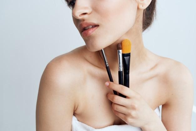 Ładna kobieta nagie ramiona kosmetyki do makijażu pędzle do pielęgnacji