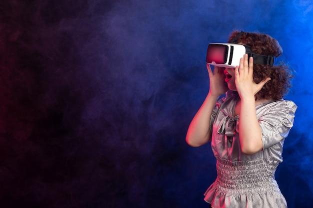 Ładna kobieta nosi zestaw słuchawkowy wirtualnej rzeczywistości na ciemnej zadymionej powierzchni