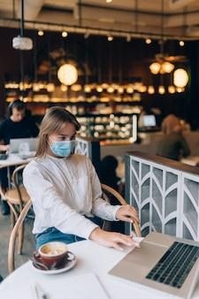 Ładna kobieta nosząca medyczną maskę na twarz używająca laptopa do pracy