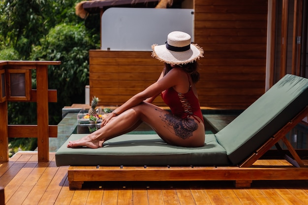 Ładna kobieta o dopasowanej, idealnie opalonej brązowej skórze ciała leży na zielonym leżaku w luksusowej tropikalnej willi w jednoczęściowym kostiumie kąpielowym ze słomkowym kapeluszem na twarzy.