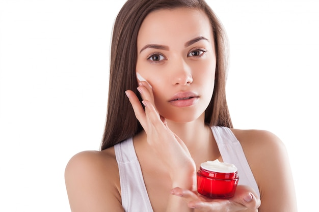 Ładna kobieta o doskonałej skórze, trzymając tubkę z kremem do twarzy. młoda dziewczyna z rękami z przodu. czerwony słoik kremu. close-up ... piękna kobieta ubrana w krem do twarzy i rąk.