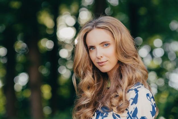 Ładna kobieta o niebieskich oczach i falujących jasnych włosach, pozuje na zewnątrz na zielonym tle,