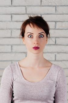 Ładna kobieta o zdziwionej twarzy, szeroko otwartych oczach mimika twarzy