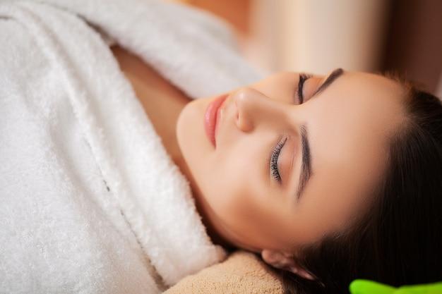 Ładna kobieta otrzymywa masaż twarzy w salonie spa