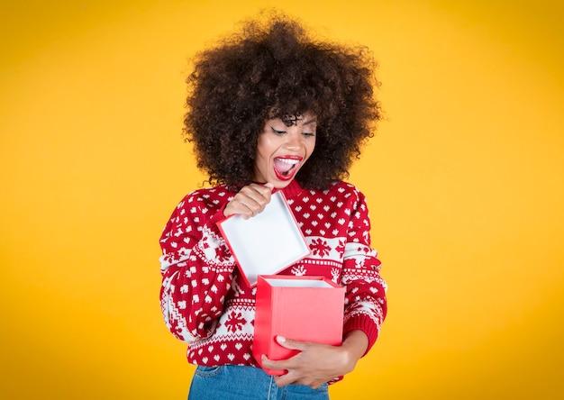 Ładna kobieta otwierająca prezent świąteczny, szczęśliwe, żółte tło