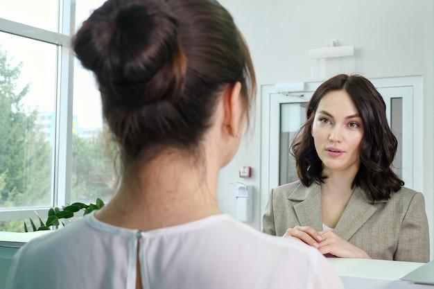 Ładna kobieta, pacjentka rozmawia z administratorem przy kasie