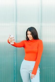 Ładna kobieta, patrząc na ekran telefonu komórkowego stoi przed ścianą