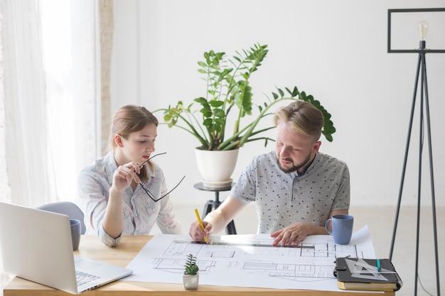 Ładna kobieta, patrząc na plan, podczas gdy jej kolega pracuje nad nim