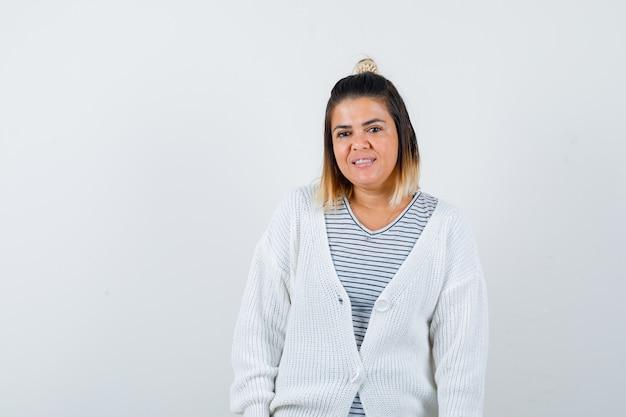Ładna kobieta patrząca na kamerę w t-shirt, sweter i genialny wygląd