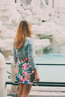 Ładna kobieta patrzeje fontanna trevi podczas jej wycieczki w rzym