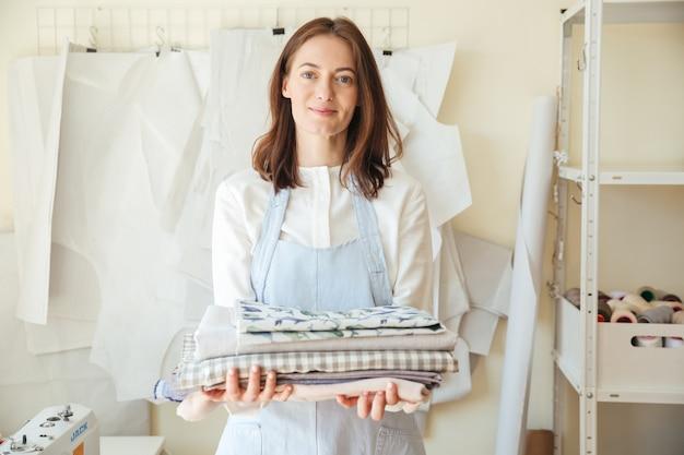 Ładna kobieta patrzeje podczas gdy trzymający stos tkaniny