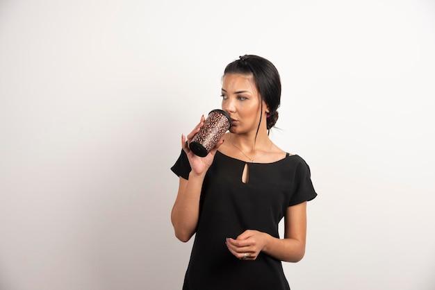 Ładna kobieta pije kawę na wynos na białej ścianie.