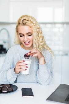 Ładna kobieta pije mleko ze szkła, jedząc ciasteczka przy użyciu komputera przenośnego, siedząc przy stole w kuchni
