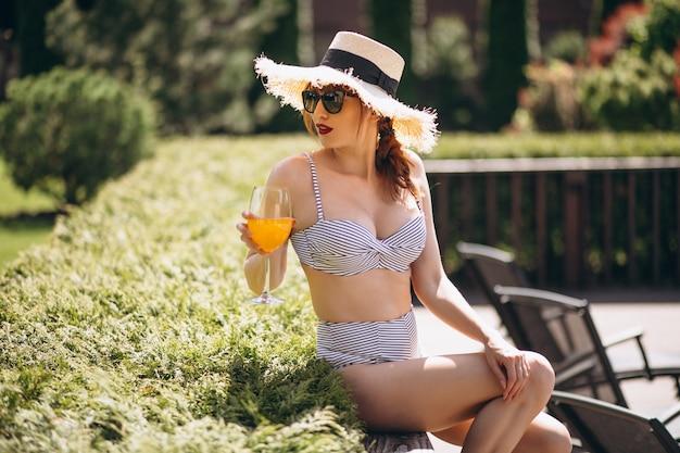 Ładna kobieta pije sok w kostium kąpielowy
