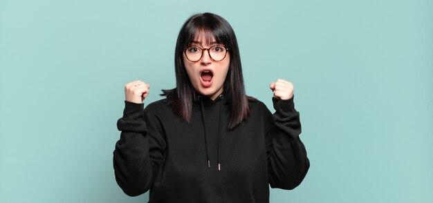 Ładna kobieta plus size agresywnie krzyczy z gniewnym wyrazem twarzy lub z zaciśniętymi pięściami świętując sukces