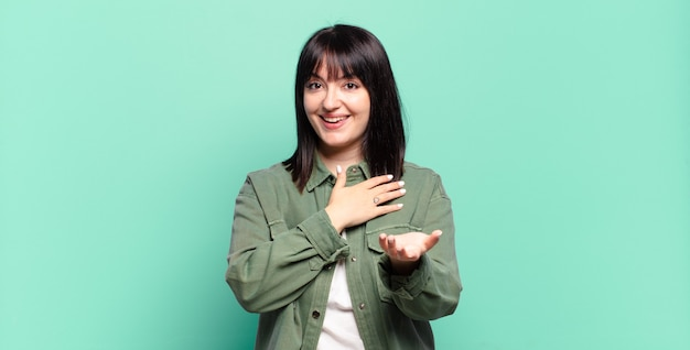 Ładna kobieta plus size czuje się szczęśliwa i zakochana, uśmiechając się jedną ręką przy sercu, a drugą wyciągniętą do przodu