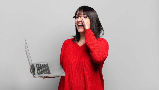 Ładna kobieta plus size czuje się szczęśliwa, podekscytowana i pozytywna, krzyczy głośno z rękami przy ustach i woła