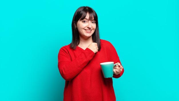 Ładna kobieta plus size czuje się szczęśliwa, pozytywna i odnosząca sukcesy, zmotywowana, gdy staje przed wyzwaniem lub świętuje dobre wyniki