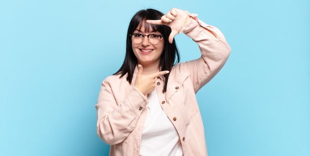 Ładna kobieta plus size czuje się szczęśliwa, przyjazna i pozytywna, uśmiechając się i robiąc rękoma portret lub ramkę na zdjęcie
