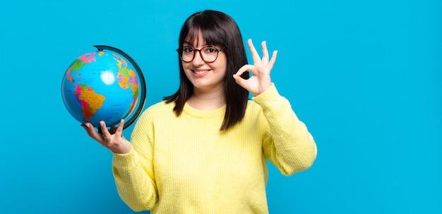 Ładna kobieta plus size czuje się szczęśliwa, zrelaksowana i usatysfakcjonowana, okazując aprobatę dobrym gestem, uśmiechając się