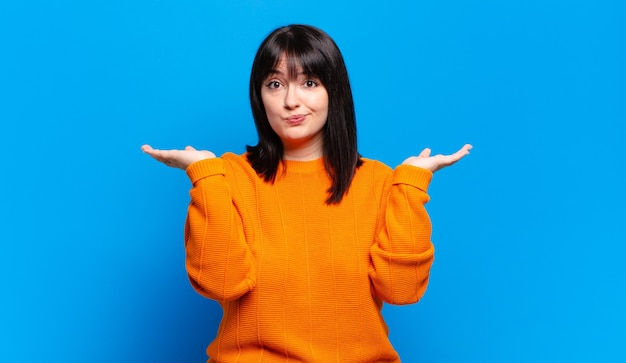 Ładna kobieta plus size czuje się zdziwiona i zagubiona, wątpi, waży lub wybiera różne opcje z zabawnym wyrazem twarzy