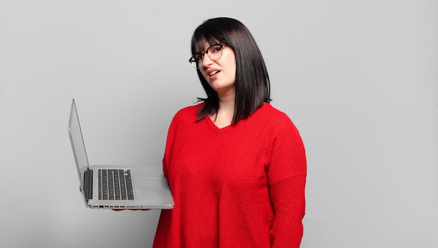 Ładna kobieta plus size czuje się zdziwiona i zdezorientowana, z głupim, oszołomionym wyrazem twarzy, patrząc na coś nieoczekiwanego