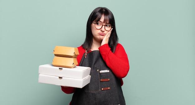 Ładna kobieta plus size czuje się znudzona, sfrustrowana i senna po męczącym, nudnym i żmudnym zadaniu, trzymając twarz ręką