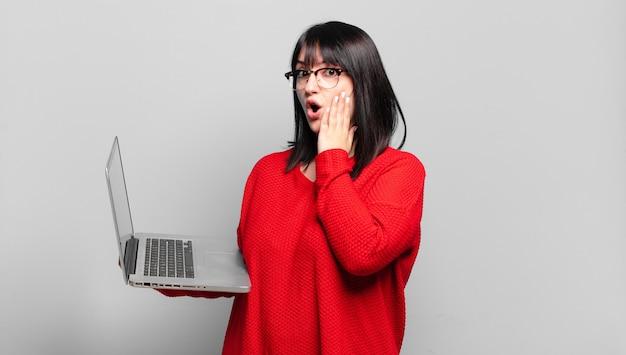 Ładna kobieta plus size czuje się zszokowana i przestraszona, wygląda na przerażoną z otwartymi ustami i rękami na policzkach