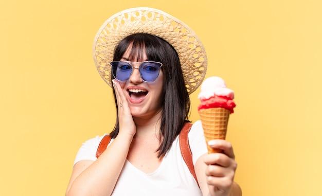 Ładna kobieta plus size na wakacjach w okularach przeciwsłonecznych, lodach i czapce