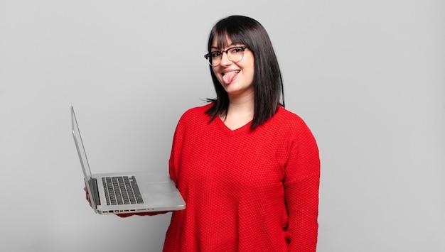 Ładna kobieta plus size o wesołej, beztroskiej, buntowniczej postawie, żartującej i wystawiającej język, bawiącej się