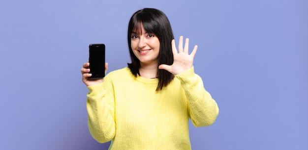 Ładna kobieta plus size, uśmiechnięta i przyjaźnie wyglądająca, pokazująca cyfrę pięć lub piąta z ręką do przodu i odliczającą
