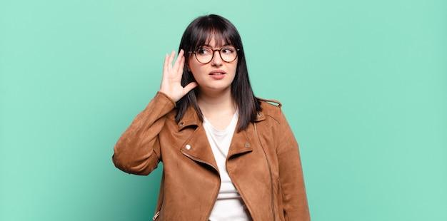 Ładna kobieta plus size wygląda poważnie i ciekawie, słucha, próbuje podsłuchać potajemną rozmowę lub plotki, podsłuchuje