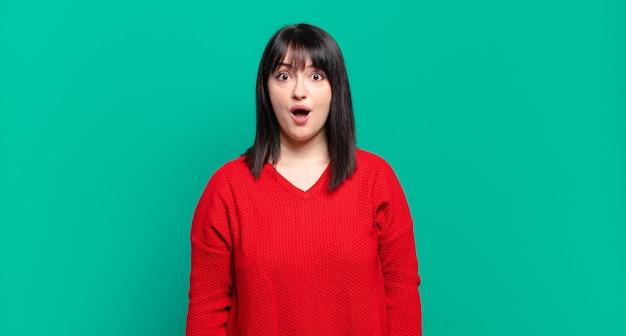 Ładna kobieta plus size wyglądająca na bardzo zszokowaną lub zaskoczoną, z otwartymi ustami i mówiącą wow