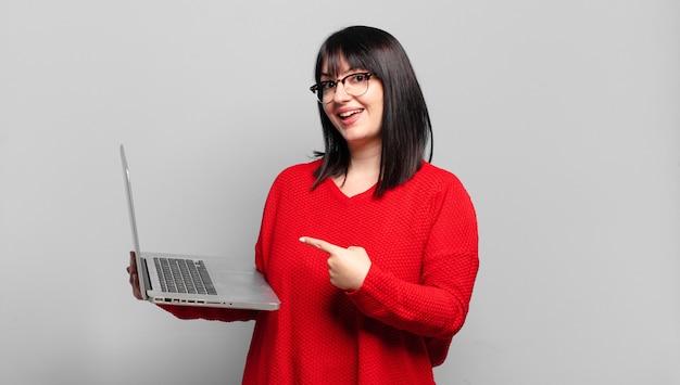 Ładna kobieta plus size wyglądająca na podekscytowaną i zaskoczoną, wskazującą na bok i do góry