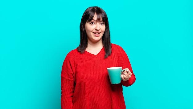 Ładna kobieta plus size wyglądająca na szczęśliwą i mile zaskoczoną, podekscytowaną, z wyrazem fascynacji i szoku