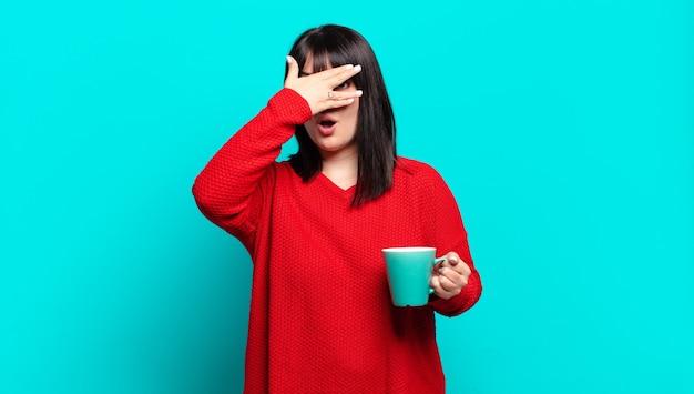 Ładna kobieta plus size wyglądająca na zszokowaną, przestraszoną lub przerażoną, zakrywającą twarz dłonią i zaglądającą między palce