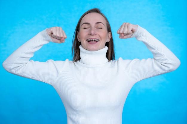 Ładna kobieta podnosi ramiona i pokazuje bicepsy, demonstrując dumę mięśni z osobistych osiągnięć na niebieskiej ścianie.