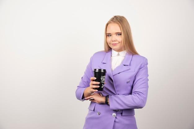 Ładna kobieta pokazując filiżankę kawy na białym