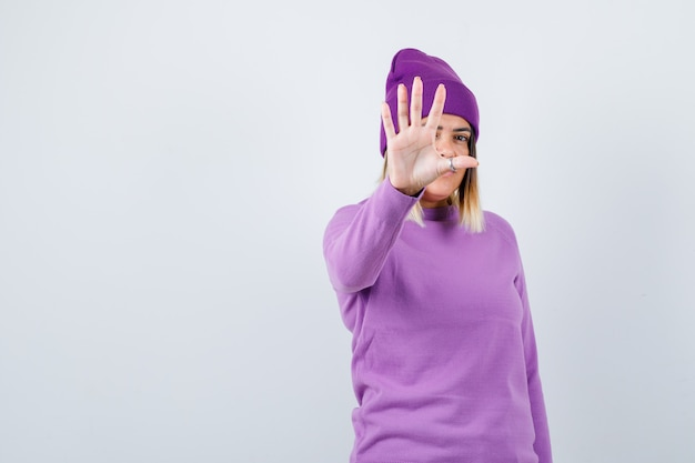 Ładna kobieta pokazując gest stop w sweter, czapka i patrząc zdecydowany. przedni widok.