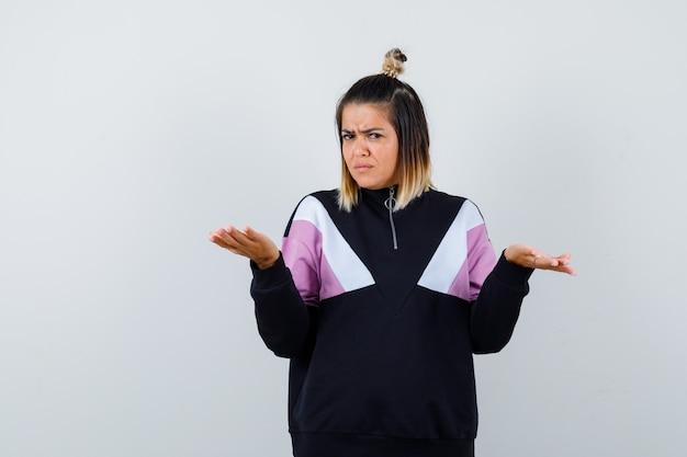 Ładna kobieta pokazująca bezradny gest w bluzie i wyglądająca na niezadowoloną