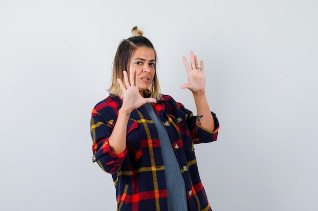 Ładna kobieta pokazująca gest kapitulacji w zwykłych ubraniach i wyglądająca na przestraszoną